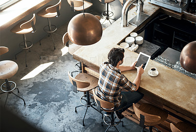 Buy stock photo High angle shot of a young man using his tablet while sitting in a coffee shop