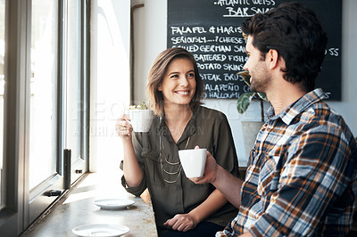 Buy stock photo Cropped shot of a young couple enjoying a cup of coffee while sitting in a coffee shop