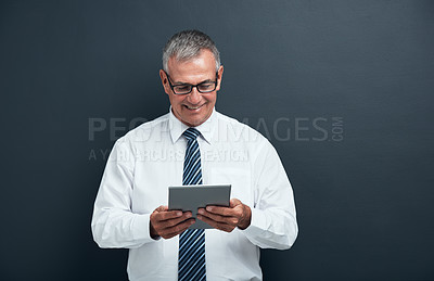 Buy stock photo Studio shot of a mature businessman using a tablet against a blue background