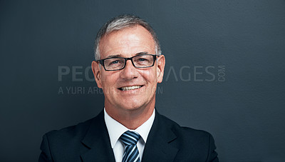 Buy stock photo Studio shot of a mature businessman posing against a blue background