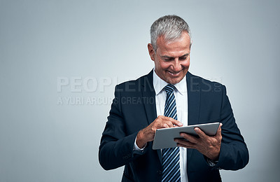 Buy stock photo Studio shot of a mature businessman using a tablet against a grey background