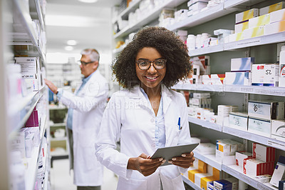 Buy stock photo Portrait of a cheerful young female pharmacist holding a digital tablet while looking at the camera in a pharmacy