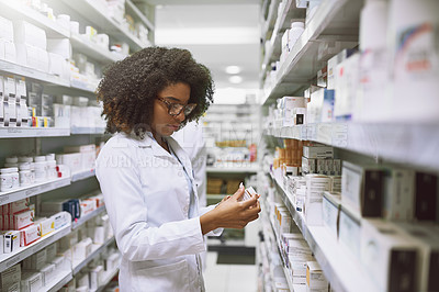 Buy stock photo Shot of a focused young female pharmacist walking around and doing stock inside of a pharmacy