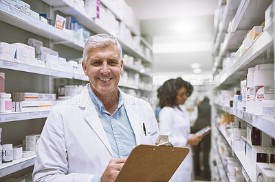 Buy stock photo Portrait of a cheerful mature male pharmacist holding a clipboard and doing stock while looking at the camera in a pharmacy
