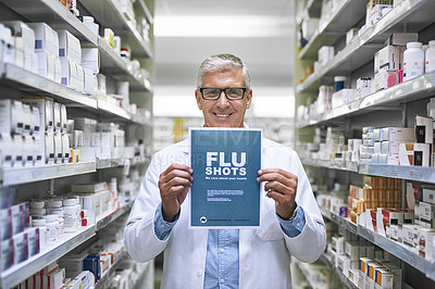 Buy stock photo Portrait of a mature male pharmacist holding up a sign indicating that you can get flu shots there