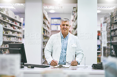 Buy stock photo Portrait of a cheerful mature male pharmacist making notes in a book on the counter while looking at the camera