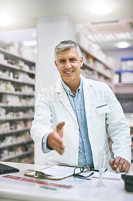 Buy stock photo Portrait of a cheerful mature male pharmacist reaching out to give a handshake while looking at the camera