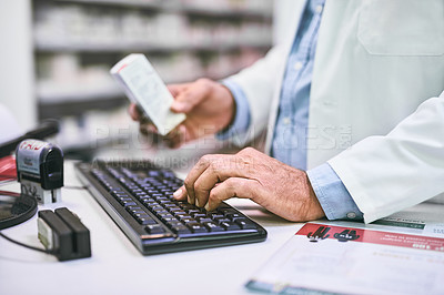 Buy stock photo Shot of a unrecognizable pharmacist typing on a computer keyboard while holding a medication subscription