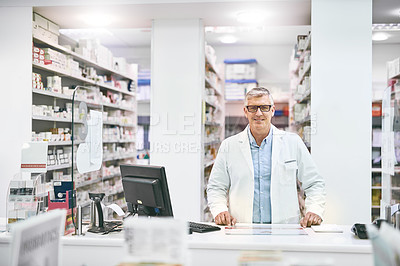 Buy stock photo Portrait of a cheerful mature male pharmacist standing behind the counter while looking at the camera in a pharmacy