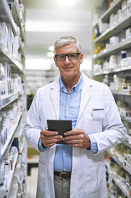 Buy stock photo Portrait of a confident mature male pharmacist making notes on a tablet while looking at the camera in a pharmacy