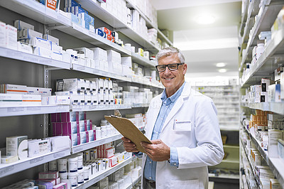 Buy stock photo Portrait of a focused mature male pharmacist making notes of the medication stock on the shelves in a pharmacy