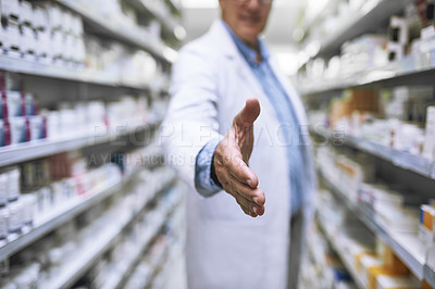 Buy stock photo Shot of a unrecognizable mature male pharmacist reaching out for a handshake in a pharmacy