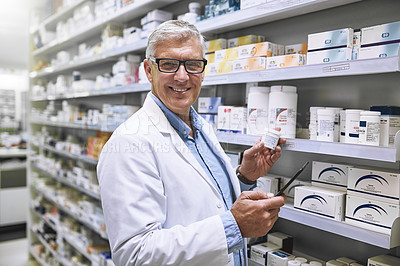 Buy stock photo Portrait of a cheerful mature male pharmacist getting medication from a shelf while looking at the camera in a pharmacy