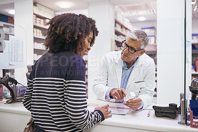 Buy stock photo Shot of a dedicated mature male pharmacist giving a customer prescription meds over the counter