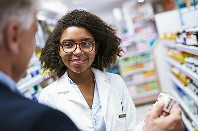 Buy stock photo Shot of a helpful young female pharmacist helping a customer with choosing the right medication in the pharmacy