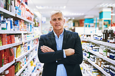 Buy stock photo Portrait of a confident well dressed mature man standing in a pharmacy with arms folded while looking at the camera