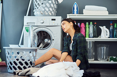 Buy stock photo Shot of an attractive young woman looking bored while doing the laundry at home