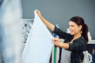 Buy stock photo Cropped shot of an attractive young woman examining a freshly washed towel while doing laundry at home