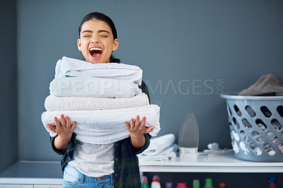 Buy stock photo Cropped shot of an attractive young woman carrying a pile of towels while doing laundry at home
