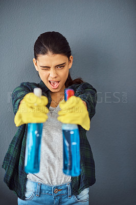 Buy stock photo Studio portrait of an attractive young woman taking aim with two spray bottles of disinfectant