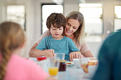 Buy stock photo Cropped shot of an attractive woman helping her son at the dining room table while having breakfast