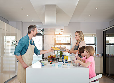 Buy stock photo Cropped shot of a happy family of four baking in their kitchen