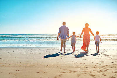 Buy stock photo Rear view shot of a family enjoying some quality time together at the beach