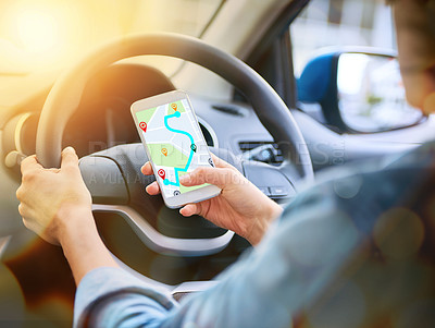 Buy stock photo Cropped shot of a woman using her phone's gps system while driving a car