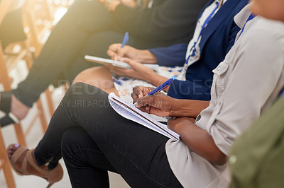 Buy stock photo Cropped shot of audience members making notes on their notepads at a conference