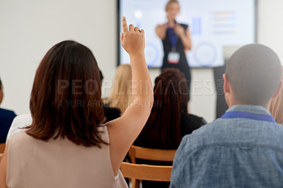 Buy stock photo Rearview shot of an audience member raising their hand to ask a question during a business conference