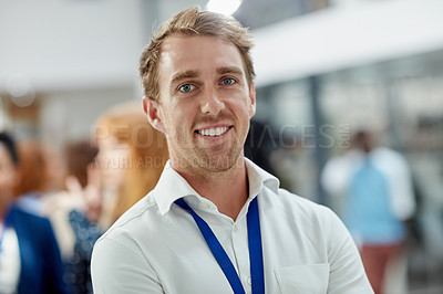 Buy stock photo Portrait of a young man standing in an office with colleagues in the background