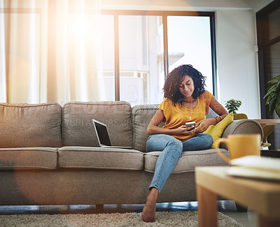 Buy stock photo Full length shot of an attractive young woman using her cellphone while relaxing at home on the weekend