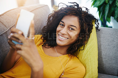 Buy stock photo High angle portrait of an attractive young woman using her cellphone while relaxing at home on the weekend