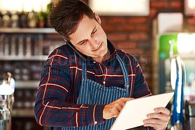 Buy stock photo Shot of a restaurant owner talking on his phone while using a digital tablet