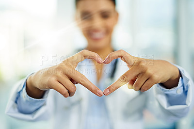 Buy stock photo Portrait of a young female doctor making a heart shape with her fingers