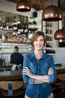 Buy stock photo Cropped portrait of an attractive businesswoman standing with her arms folded in her coffee shop