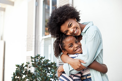 Buy stock photo Portrait of a cheerful mother and daughter giving each other a hug while looking at the camera outside during the day