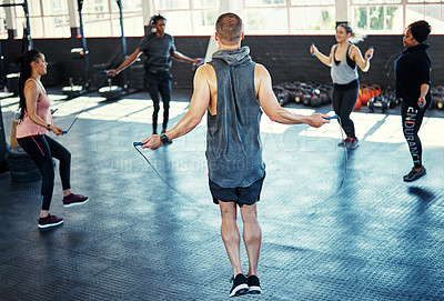 Buy stock photo Shot of a fitness group doing rope exercises in their session at the gym