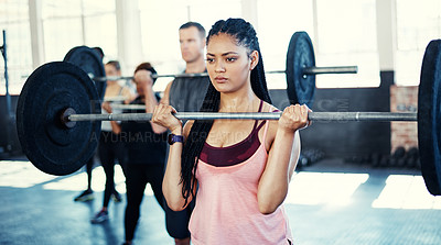 Buy stock photo Shot of a woman working out with a barbell in her session at the gym