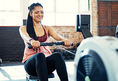 Buy stock photo Shot of a happy young woman working out on a rowing machine