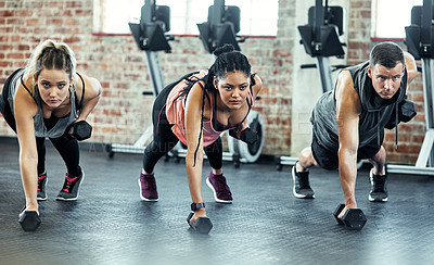 Buy stock photo Shot of a fitness group using dumbbells in their session at the gym