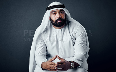 Buy stock photo Studio shot of a young man dressed in Islamic traditional clothing posing against a dark background