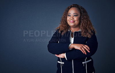 Buy stock photo Studio shot of a cheerful young businesswoman standing with her arms folded while standing against a blue background