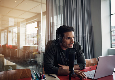 Buy stock photo Shot of a young man recording a podcast on a laptop in a modern office