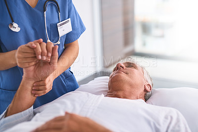Buy stock photo Shot of a relaxed mature male patient lying on a hospital bed while his hand gets held by a doctor