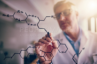 Buy stock photo Shot of a focused mature male scientist solving equations on a glass wall in a laboratory