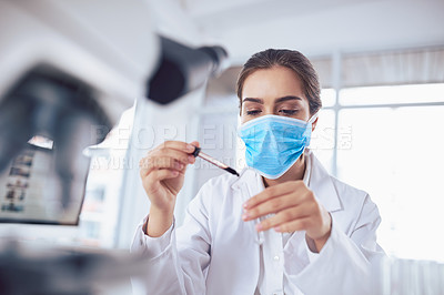 Buy stock photo Shot of a focused young female scientist wearing a surgical mask and doing an experiment while being seated inside a laboratory