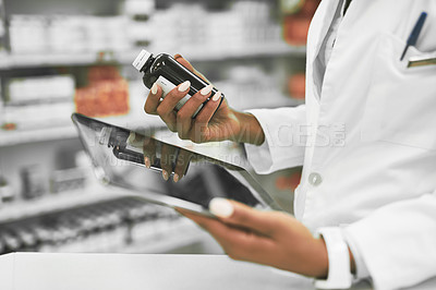 Buy stock photo Shot of a unrecognisable female pharmacist holding a digital tablet in one hand and medication in the other inside of a pharmacy