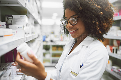 Buy stock photo Shot of a cheerful young female pharmacist reading the label of a medication bottle inside of a pharmacy