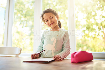 Buy stock photo Portrait of a focused little girl drawing pictures in a book while looking at the camera at home
